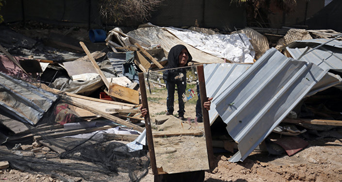 A woman from the Arab Jahalin Bedouin community carries a mirror after the demolition of her home in the West Bank Bedouin camp of al-Khan al-Ahmar on April 7, 2016