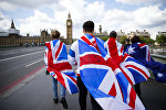 People walk over Westminster Bridge wrapped in Union flags, towards the Queen Elizabeth Tower (Big Ben) and The Houses of Parliament in central London on June 26, 2016