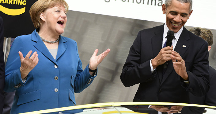 US President Barack Obama (R) and German Chancellor Angela Merkel share a laugh at the booth of Harting technology group as they tour the Hanover industrial Fair in Hanover, central Germany, on April 25, 2016