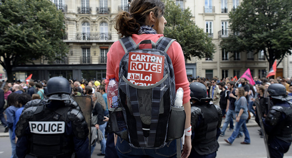 A woman carrying a backpack with a sticker reading Red card to the labour law stands behind French CRS anti-riot police during a demonstration against the government's proposed labour reforms in Paris on July 5, 2016