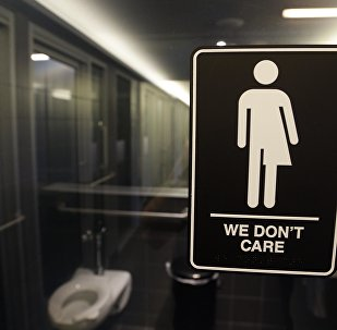 This Thursday, May 12, 2016, file photo, shows signage outside a restroom at 21c Museum Hotel in Durham, N.C. North Carolina is in a legal battle over a state law that requires transgender people to use the public restroom matching the sex on their birth certificate.