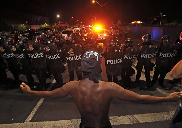 A protester raises him arms in front of a police blockade as marchers take to the streets to demonstrate against the recent fatal shootings of black men by police, Friday, July 8, 2016, in Phoenix.