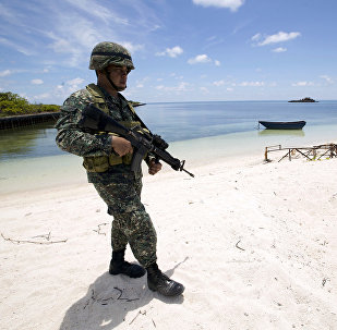 A Filipino soldier patrols at the shore of Pagasa island (Thitu Island) in the Spratly group of islands in the South China Sea, west of Palawan, Philippines, May 11, 2015.