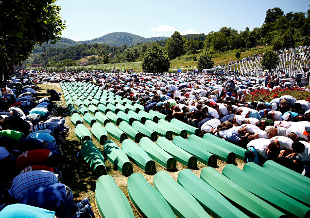 Muslim men pray in front of coffins during mass funeral in Potocari near Srebrenica, Bosnia and Herzegovina July 11, 2016