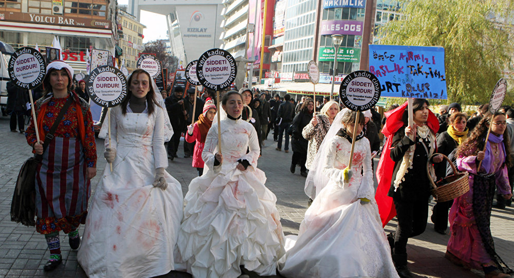 Women activists, some dressed in wedding gowns representing child brides forced into marriage, hold placards that read End violence to protest rape and domestic violence.