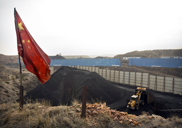 Chinese flag stands in the breeze as a loader moves coal at a coal mine near Ordos in northern China (File)