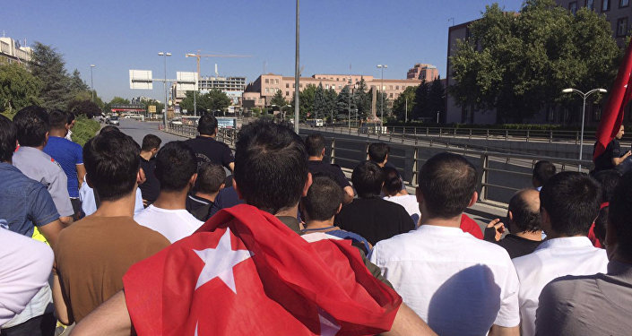 People with the Turkish national flags gather outside the military headquarters in Ankara, Turkey, Saturday July 16, 2016.