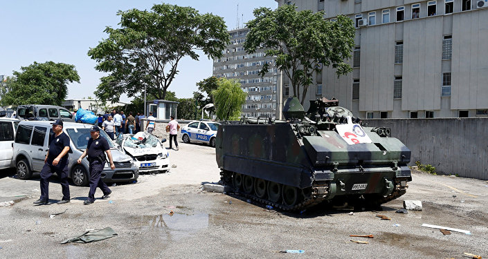 Damaged cars are seen next to an armored military vehicle in front of the police headquarters in Ankara, Turkey, July 18, 2016.