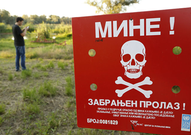 A Bosnian man plays the Pokemon game on his phone as he stands near a sign warning of a Minefield, near the Bosnian town of Brcko, on Tuesday, July 19, 2016