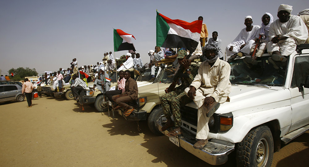 Sudanese wave national flags during a rally organised during the visit of Sudanese president in the town of Zalingei, capital of Central Darfur state on April 3, 2016