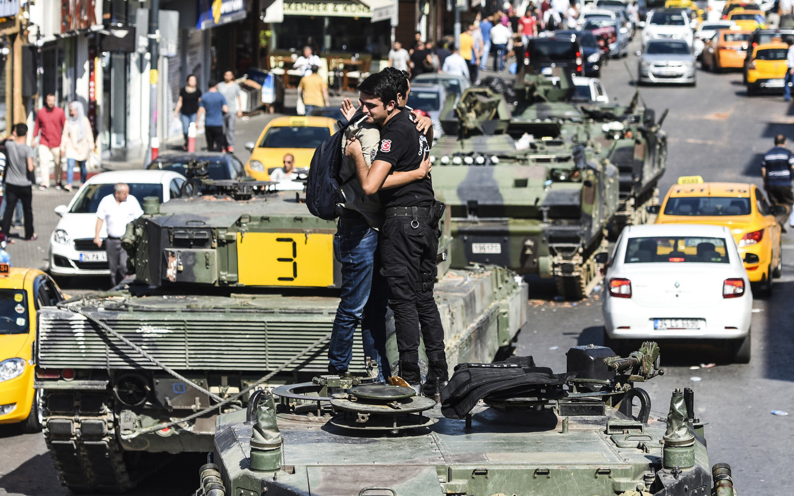 Turkish police officer (R) embrace a man on a tank after the military position was taken over at the Anatolian side at Uskudar in Istanbul on July 16, 2016