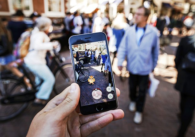 Gamers play with the Pokemon Go application on their mobile phone, at the Grote Markt in Haarlem, on July 13, 2016