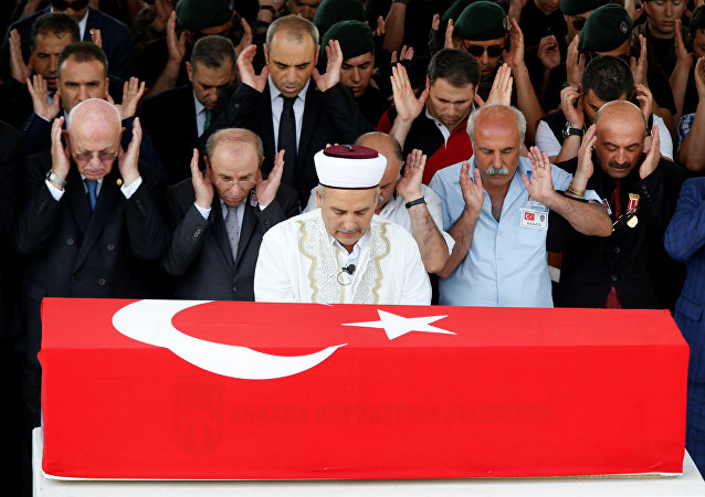People pray during a funeral ceremony for two Turkish police officers who were killed in the thwarted coup in Ankara, Turkey, July 20, 2016