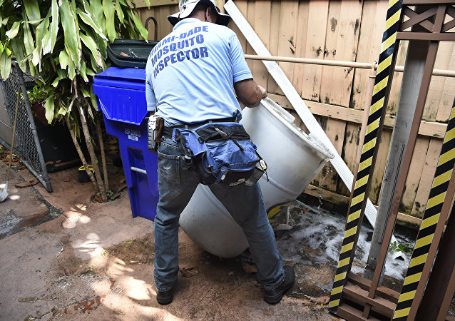 Miami-Dade mosquito control worker Carlos Vargas dumps a barrel of standing water that can incubate the Aedes aegypti mosquito larvae at a home in Miami, Florida, on June 08, 2016