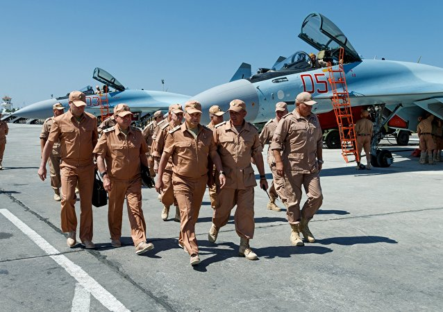 Russian Defense Minister Sergei Shoigu, center, inspects military service conditions for Russian personnel at the Hmeimim air base, during his working visit to Syria