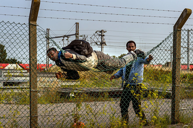 A migrant climbs over a fence in Coquelles, near Calais northern France,