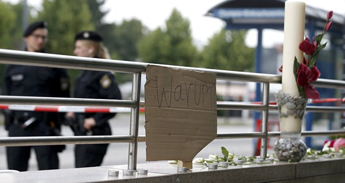 A sign reading 'Why' and flowers are placed on on a wall near the Olympia shopping mall, where yesterday's shooting rampage started, in Munich, Germany July 23, 2016.