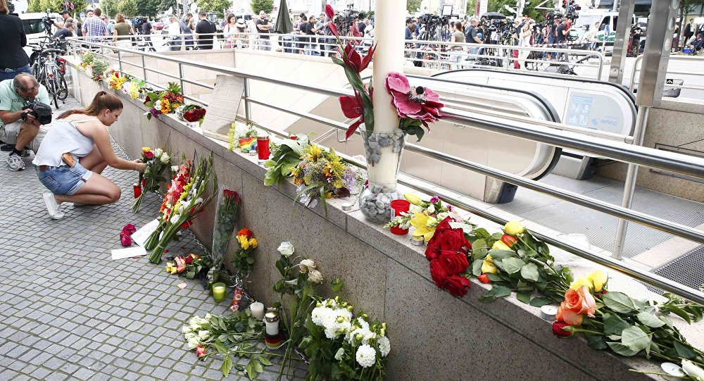 A women places flowers near the Olympia shopping mall, where yesterday's shooting rampage started, in Munich, Germany July 23, 2016.