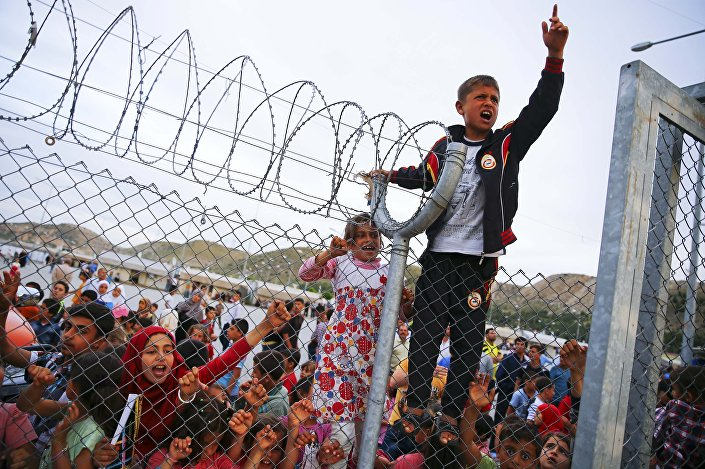 Refugee youths gesture from behind a fence at Nizip refugee camp near Gaziantep, Turkey, April 23, 2016.