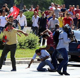 Supporters of Turkey's President Recep Tayyip Erdogan, who were staging a protest against a coup, clash with Turkish journalists near the Turkish military headquarters, in Ankara, Turkey, Saturday, July 16, 2016