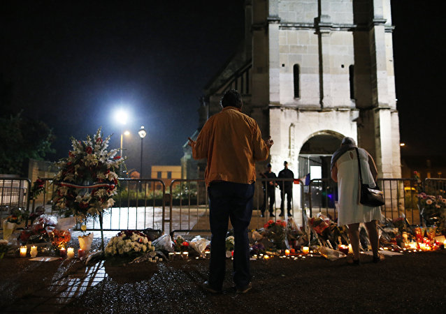 People stand in front of a makeshif memorial near two gendarmes guarding the Saint-Etienne du Rouvray church on July 27, 2016, after the priest Jacques Hamel was killed on July 26 in the church during a hostage-taking claimed by Islamic State group