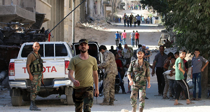 Syrian government forces secure a street as civilians walk on a street in the neighbourhood of Bani Zeid, on Aleppo's northern outskirts on July 29, 2016