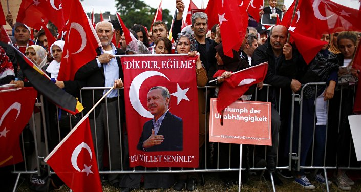 Supporters of Turkish President Tayyip Erdogan hold Turkish flags during a pro-government protest in Cologne, Germany