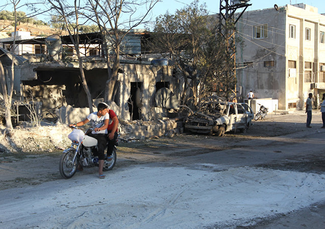 People inspect the damage as they stand near a Save the Children sponsored maternity hospital after an airstrike in the rebel-controlled town of Kafer Takhareem in Idlib province, Syria
