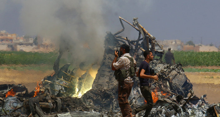 Men inspect the wreckage of a Russian helicopter that had been shot down in the north of Syria's rebel-held Idlib province, Syria
