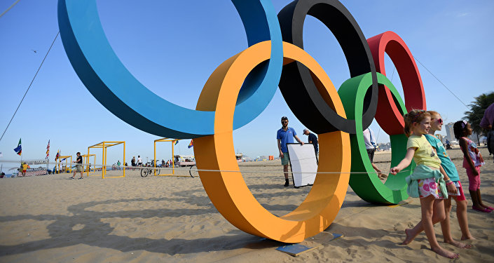 Children pose next to the Olympic rings on Copacabana beach in Rio de Janeiro on August 1, 2016 ahead of the 2016 Rio Olympic Games
