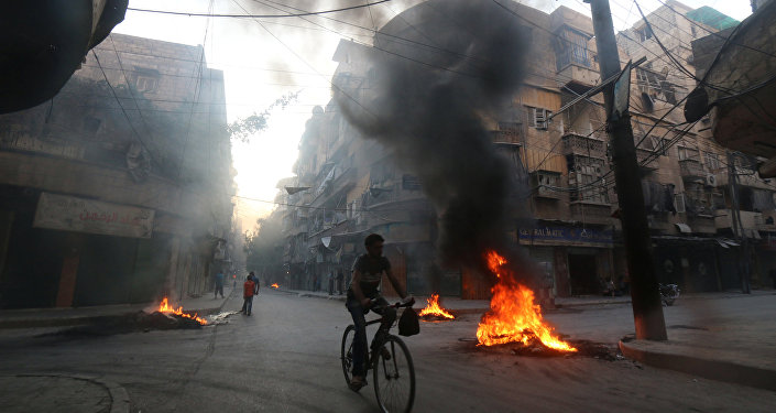 A man rides a bicycle past burning tyres, which activists said are used to create smoke cover from warplanes, in Aleppo, Syria August 1, 2016