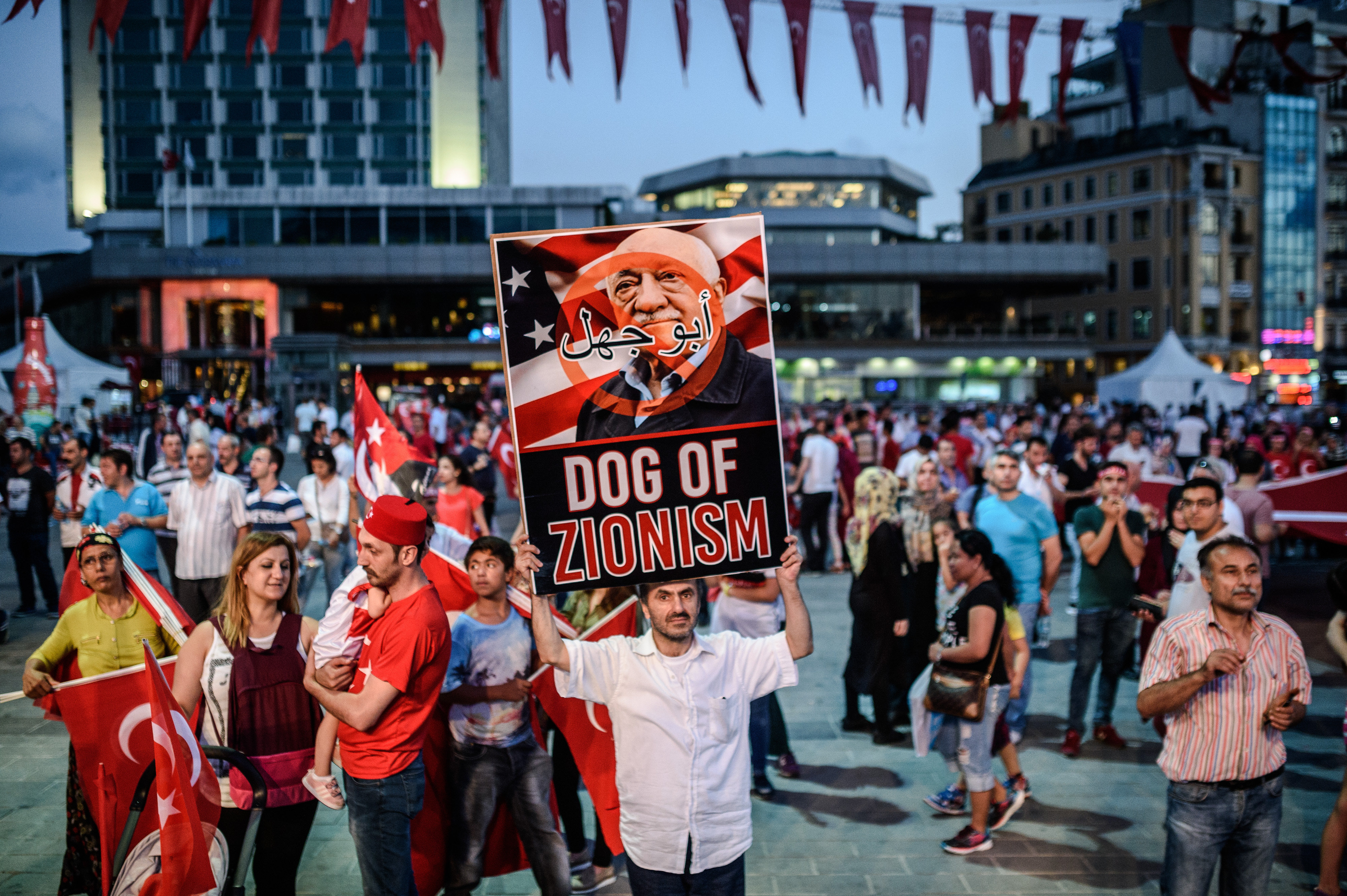 A Pro-Erdogan supporter holds a portrait of US-based cleric Fethullah Gulen during a rally against the military coup on Taksim square in Istanbul on July 25, 2016