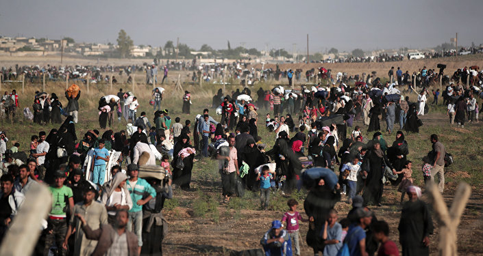 In this June 14, 2015 file photo taken from the Turkish side of the border between Turkey and Syria, in Akcakale, Sanliurfa province, southeastern Turkey, thousands of Syrian refugees walk in order to cross into Turkey