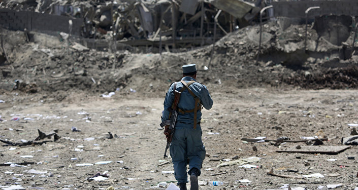 FILE - In this Monday, Aug. 1, 2016 file photo, an Afghan Security policeman inspects the site of a suicide truck bombing, in Kabul, Afghanistan.