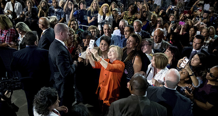 Democratic presidential candidate Hillary Clinton takes a photo with a member of the audience after speaking at a rally at Osceola Heritage Park, in Kissimmee, Fla., Monday, Aug. 8, 2016.