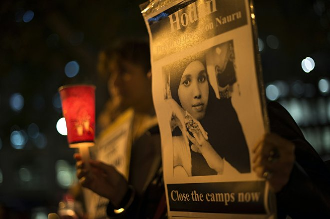 A participant holds portrait of a Somali refugee, who set herself on fire on the remote Pacific island of Nauru, during a candle light vigil in Sydney on May 4, 2016