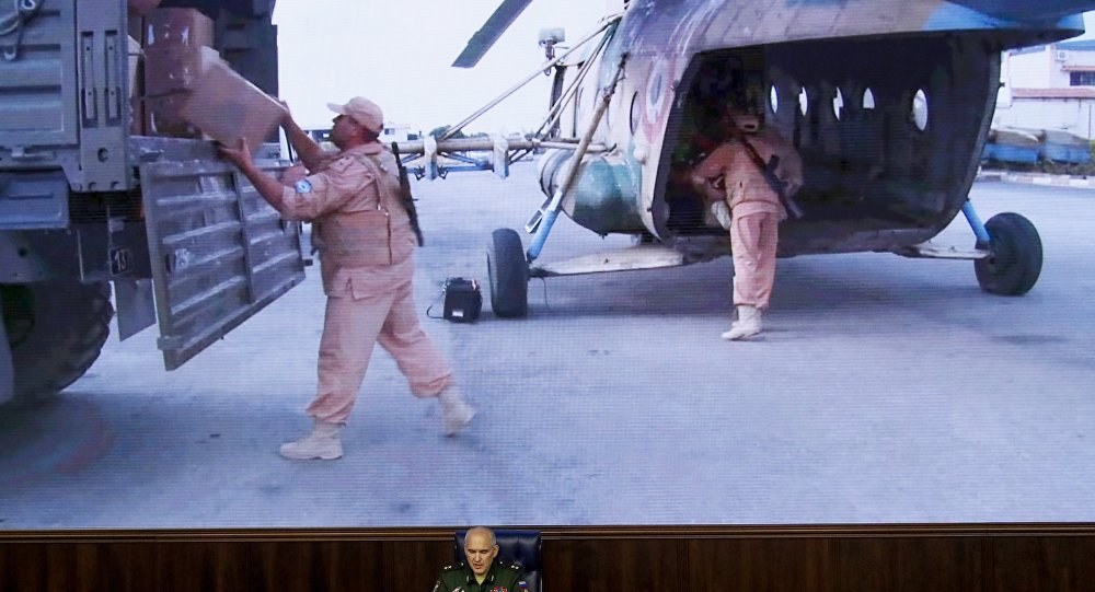 Lt.-Gen. Sergei Rudskoi of the Russian Military General Staff, speaks to the media as Syrian army soldiers load a humanitarian aid at Aleppo is displayed on screen at a Russian Defense Ministry building in Moscow, Russia, Monday, Aug. 1, 2016