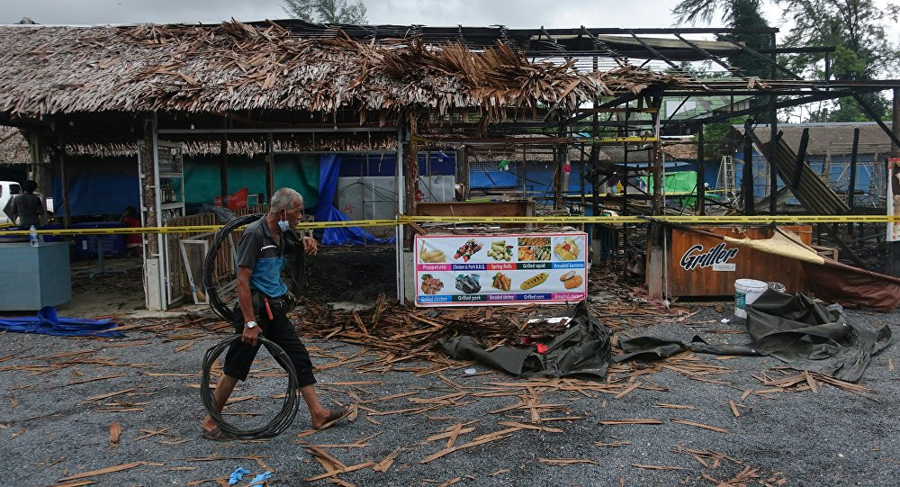 A man walks past the site of a small bomb blast and arson attack on Bang Niang market, Takua Pa, near Khao Lak in Phang Nga province of Thailand on August 12, 2016
