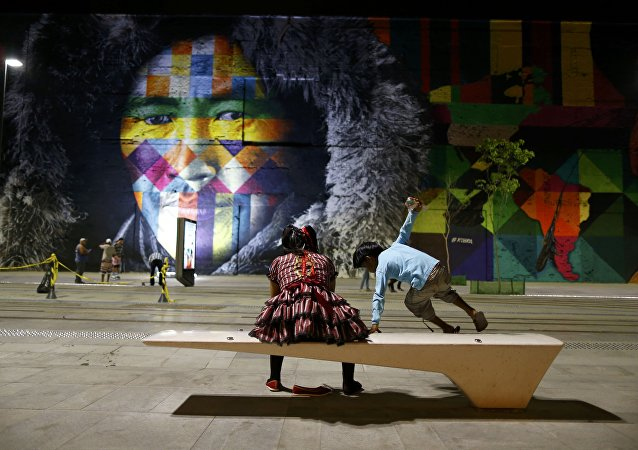 2016 Rio Olympics - Locals sit in front of a mural created by Brazilian artist Eduardo Kobra that covers nearly 3,000 square meters of wall space Rio de Janeiro, Brazil