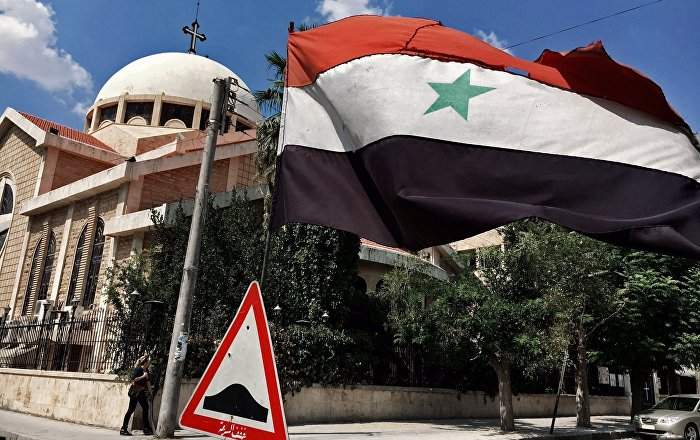 A state flag of the Syrian Arab Republic by an Orthodox church in an old Christian block of Aleppo, Syria