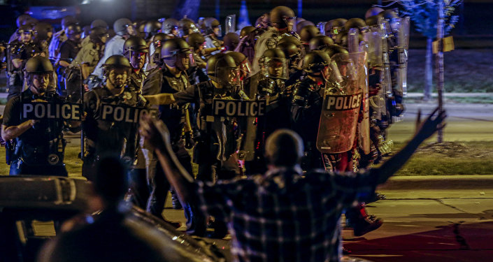 Police move in on a group of protesters throwing rocks at them in Milwaukee, Sunday, Aug. 14, 2016