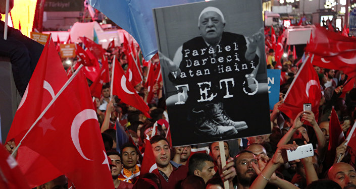 Supporters of Turkish President Recep Tayyip Erdogan wave their national flags and hold a portrait of Fethullah Gulen, a U.S.-based Muslim cleric with Turkish words that read: the Coup nation traitor, FETO (Feto is the nickname of Fethullah Gulen), during a pro-government rally at Kizilay main square, in Ankara, Turkey, Wednesday, July 20, 2016