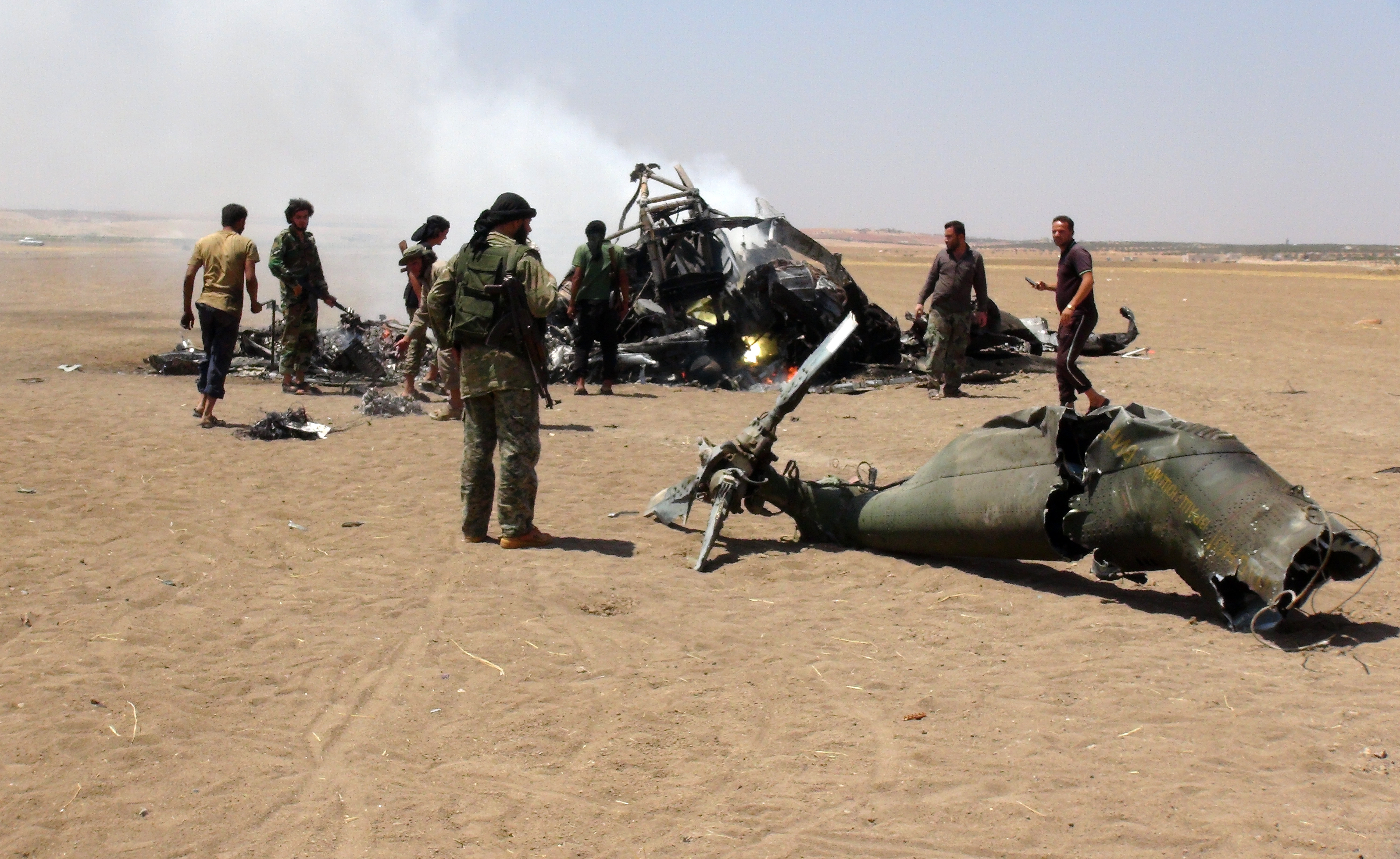 A picture taken on August 1, 2016 shows Syrian rebels gathering around the wreckage of a Russian Mi-8 military transport helicopter after it was shot down along the administrative border between Idlib province, northwestern Syria and neighbouring Aleppo