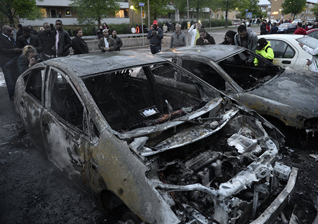 People react as they stand around cars gutted by fire in the Stockholm suburb of Rinkeby after youths rioted in several different suburbs around Stockholm, Sweden for a fourth consecutive night on May 23, 2013.