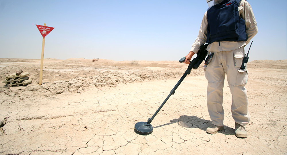 An Iraqi man wearing protective gear searches for landmines in the Shalamja border crossin, west of Basra, on the border between Iraq and Iran