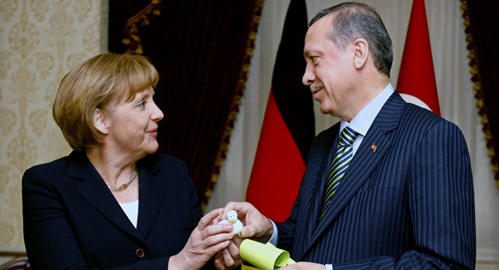 German Chancellor Angela Merkel, left, and Turkish President Recep Tayyip Erdogan exchange gifts before their talks