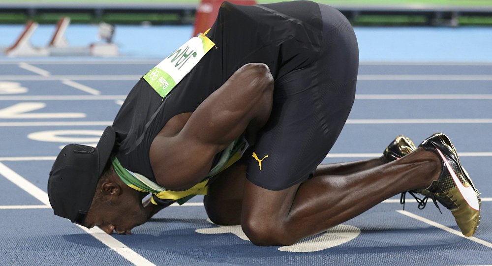 2016 Rio Olympics - Athletics - Final - Men's 4 x 100m Relay Final - Olympic Stadium - Rio de Janeiro, Brazil - 19/08/2016. Usain Bolt (JAM) of Jamaica kisses the track after his team won the gold