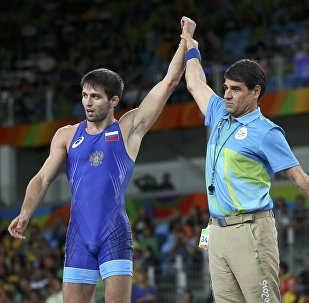 2016 Rio Olympics - Wrestling - Semifinal - Men's Freestyle 65 kg Semifinal - Carioca Arena 2 - Rio de Janeiro, Brazil - 21/08/2016. The referee raises the hand of Soslan Ramonov (RUS) of Russia after his victory against Ikhtiyor Navruzov (UZB) of Uzbekistan