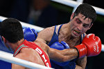 From right: Misha Aloyan (Russia) and Shakhobiddin Zairov (Uzbekistan) during the final bout of the men's boxing in the 52kg division at the XXXI Summer Olympics