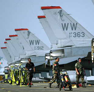 United States Air Force pilots and crews walk beside F-16 aircrafts parked on the tarmac during the Cope India 05 Indo-US joint military exercise, at the Kalaikunda Air Base, some 130 kms south west of Kolkata, 17 November 2005